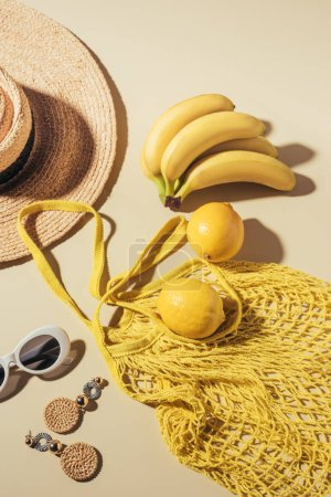 top view of wicker hat, sunglasses, earrings and yellow string bag with bananas and lemons