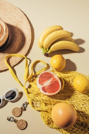 top view of wicker hat, sunglasses, earrings and yellow string bag with fresh ripe fruits