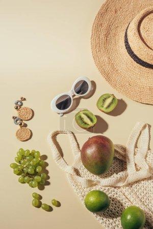 vue de dessus du chapeau en osier, des lunettes de soleil, des boucles d'oreilles et du sac à ficelle avec des fruits frais