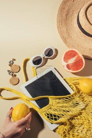 cropped shot of human hand holding lemon, digital tablet, string bag and sunglasses on brown