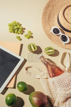top view of sunglasses, hat, digital tablet and string bag with drink and fruits
