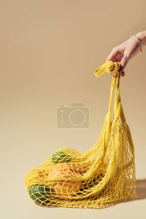 partial view of person holding yellow string bag with fresh fruits on brown