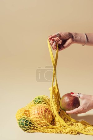 cropped shot of person holding yellow string bag and fresh fruits on brown