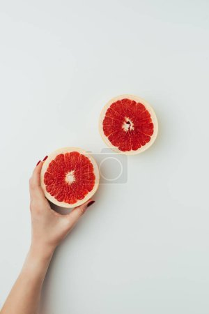 Photo for Partial view of woman holding grapefruit halves, on grey - Royalty Free Image