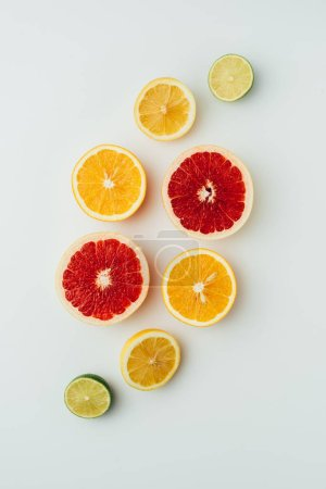 top view of grapefruit, lemon, lime and orange slices, on grey