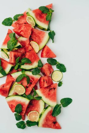 top view of red juicy watermelon and lime slices with mint leaves, on grey background