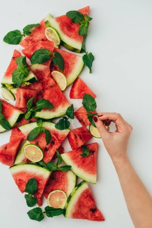 cropped view of woman putting mint leaves on background made of watermelon and lime slices, on grey