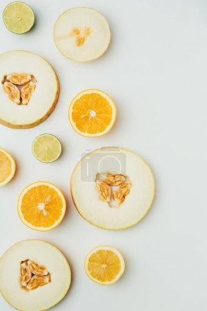 top view of melon, lime and orange slices, on grey background