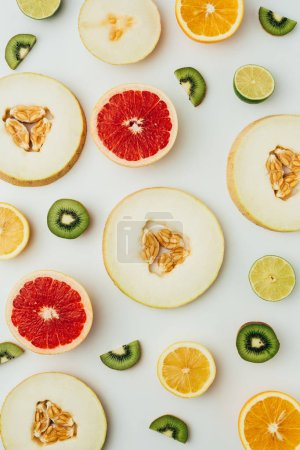 top view of fresh melon, lime, grapefruit and kiwi slices, on grey background