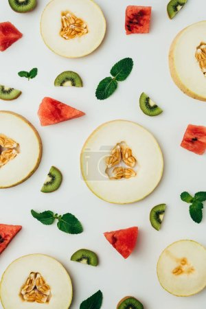 top view of juicy melon, watermelon and kiwi slices with mint leaves, on grey background