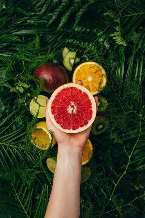 Photo pour Vue recadrée de la femme tenant la moitié du pamplemousse sur les fruits sur les feuilles de palmier - image libre de droit