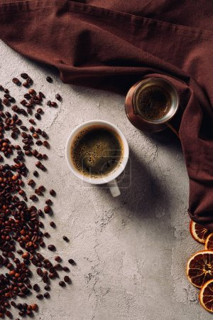 Photo for Top view of cup of coffee with cezve and coffee beans on concrete surface - Royalty Free Image
