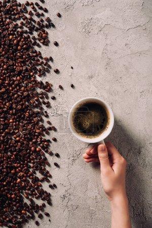 Photo pour Photo recadrée de femme tenant la tasse de café sur la surface du béton avec des grains de café renversées - image libre de droit