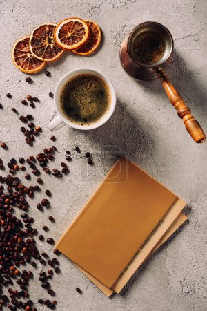 top view of cup and cezve of coffee with book on concrete surface
