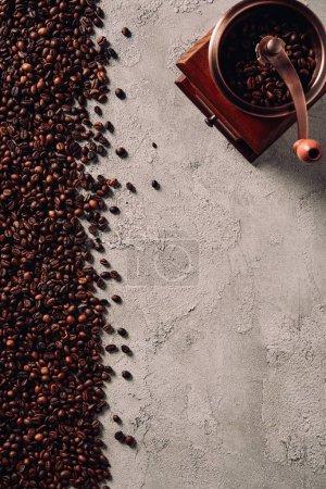 Photo pour Vue de dessus des grains de café renversés avec broyeur vintage sur la surface du béton - image libre de droit