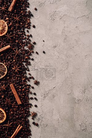 top view of spilled coffee beans with various spices on concrete surface