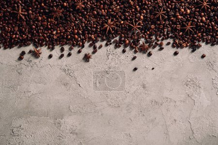 Photo for Top view of spilled coffee beans with anise on concrete surface - Royalty Free Image
