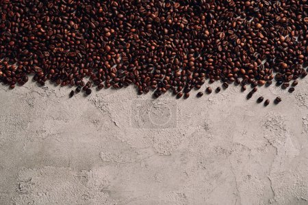 top view of spilled coffee beans on concrete tabletop