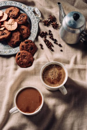 Photo for Top view of cups of fresh coffee with chocolate chip cookies and vintage metal pot on beige cloth - Royalty Free Image