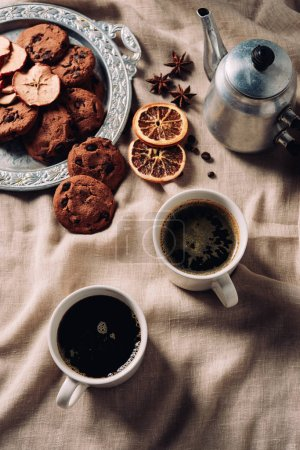 top view of cups of coffee with chocolate chip cookies and vintage metal pot on beige cloth