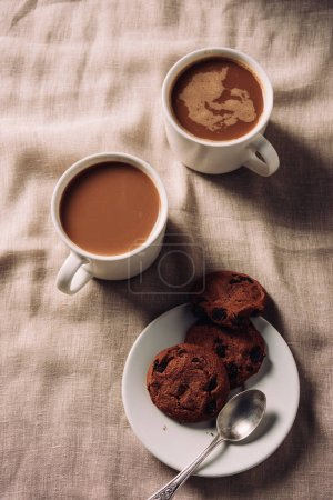 Photo for Top view of cups of coffee with chocolate chip cookies on plate on beige cloth - Royalty Free Image