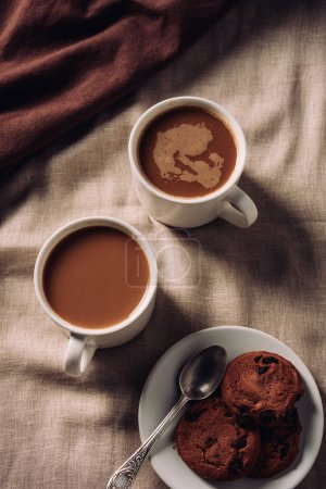 Photo for Top view of cups of coffee with chocolate chip cookies on beige cloth - Royalty Free Image