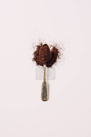 Photo for Top view of metal spoon with grinded coffee on white surface - Royalty Free Image