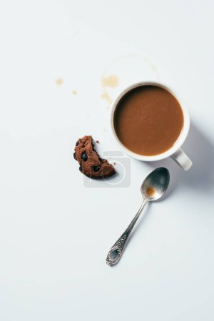 Photo for Top view of cup of coffee with bitten chocolate chip cookie and spoon on white surface - Royalty Free Image