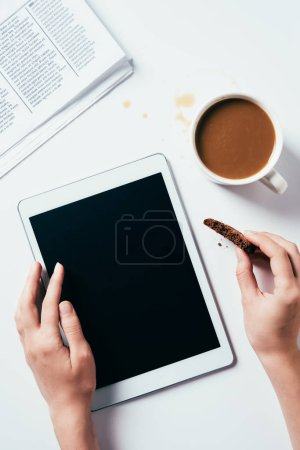 Photo for Cropped shot of woman using tablet while eating chocolate chip cookie with coffee on white surface - Royalty Free Image