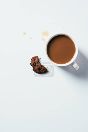 Photo for Top view of cup of coffee with bitten chocolate chip cookie on white surface - Royalty Free Image