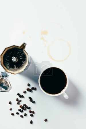 top view of cup of black coffee with mocha pot on messy white surface