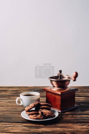 Photo for Cup of coffee with vintage grinder and chocolate chip cookies on rustic wooden table - Royalty Free Image