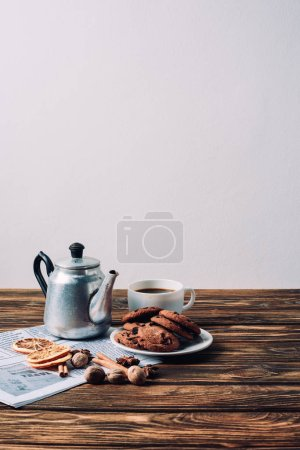 Photo for Cup of coffee with vintage metal pot and spices on rustic wooden table - Royalty Free Image