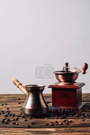 Photo for Vintage cezve and coffee grinder with coffee beans on rustic wooden table - Royalty Free Image