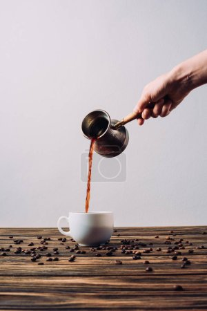 Photo for Cropped shot of woman pouring coffee into cup from cezve on rustic wooden table - Royalty Free Image