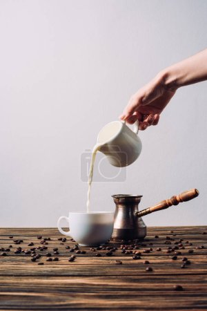 cropped shot of woman pouring milk into coffee on rustic wooden table