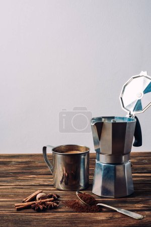 Photo for Metal mug of coffee with mocha pot and spices on rustic wooden table - Royalty Free Image