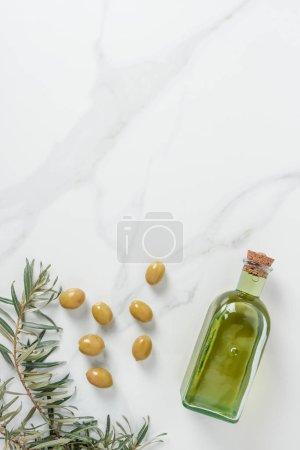 top view of bottle of olive oil, twigs and olives on marble table