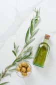 top view of bottle of olive oil and olives in bowl on marble table