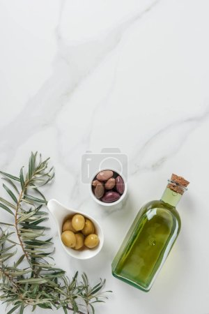 top view of olive oil and yummy olives in bowls on marble table