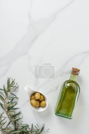 top view of bottle of olive oil and olives in bowl on marble surface