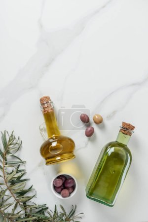 top view of olive oil in glass bottles and olives on marble table