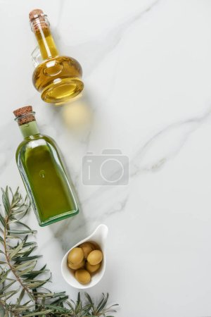 top view of olive oil in glass bottles and olives on marble tabletop