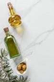 vue de dessus d'huile d'olive dans des bouteilles en verre et les olives sur le dessus de table en marbre