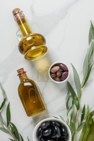 top view of olive oil in glass bottles and olives on white surface