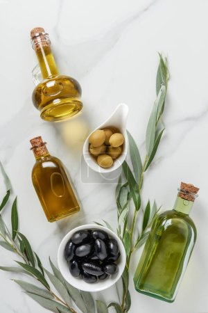 Photo for Top view of olive oil in glass bottles and tasty olives on marble table - Royalty Free Image