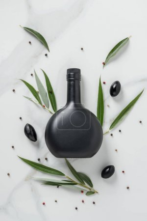 Photo for Top view of black bottle of olive oil and olives on marble table - Royalty Free Image