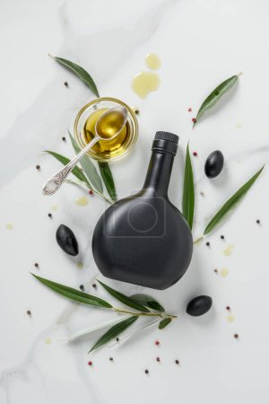 Photo for Top view of black bottle of olive oil and glass with spoon on marble table - Royalty Free Image