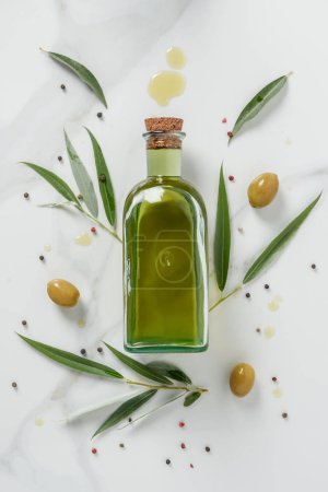 Photo for Food styling of olive oil bottle and olives on marble table - Royalty Free Image