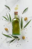 food styling of olive oil bottle and olives on marble table
